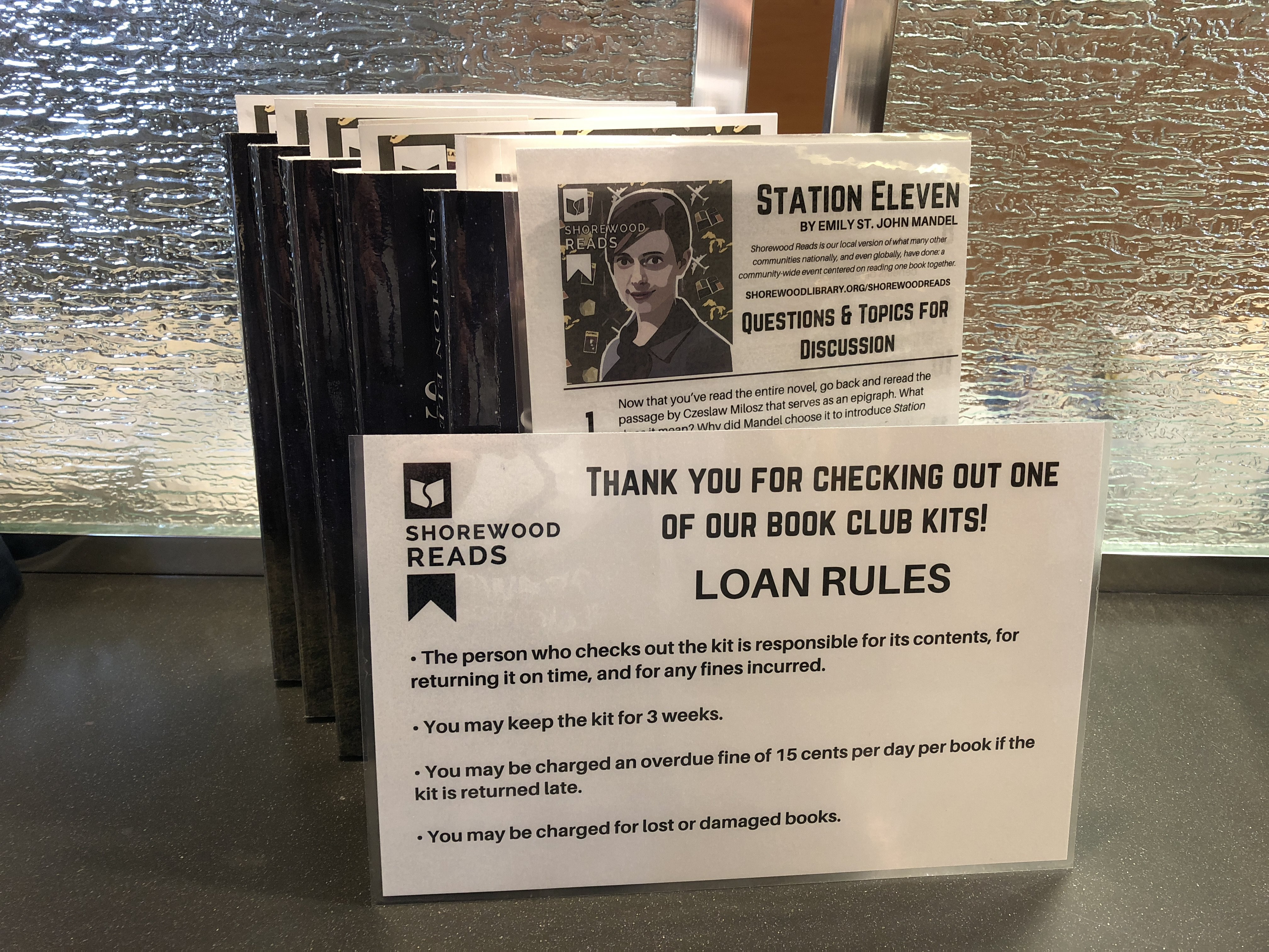 Copies of Station Eleven by a Shorewood Reads Loan Rules sign propped.